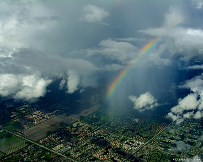 A rainbow forms in a narrow sweeping shower over Boca Raton