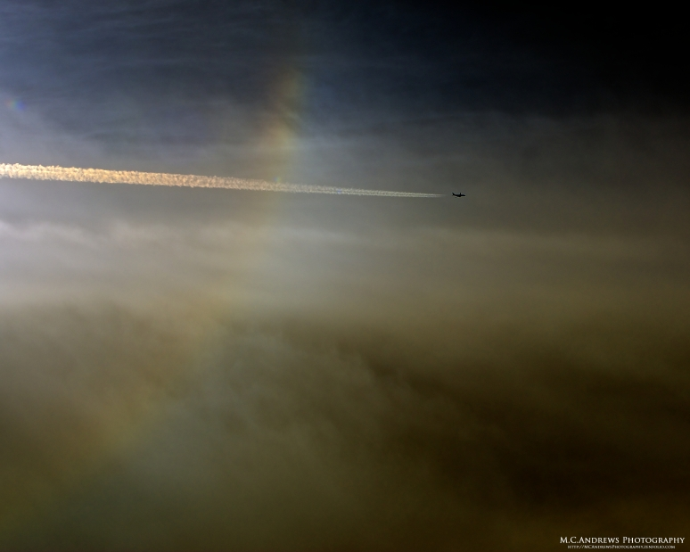 Contrail through sun dog